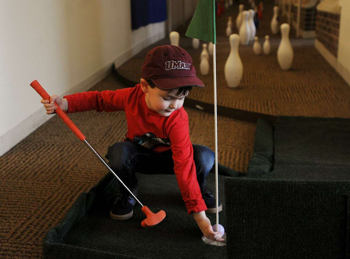 Landon Kroszner, 4, of Trumbull, grabs his ball after playing the ninth hole during the event. Friends of the Library Mini-Golf fundraiser at the Fairfield Public Library in Fairfield, Conn. on Sunday, March 25, 2018. Holes were laid out through the stacks and down stairways and ramps throughout the building.