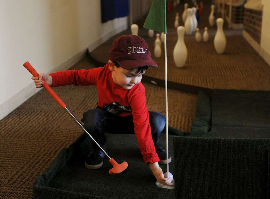 Landon Kroszner, 4, of Trumbull, grabs his ball after playing the ninth hole during the event. Friends of the Library Mini-Golf fundraiser at the Fairfield Public Library in Fairfield, Conn. on Sunday, March 25, 2018. Holes were laid out through the stacks and down stairways and ramps throughout the building. Photo: Brian A. Pounds / Hearst Connecticut Media / Connecticut Post