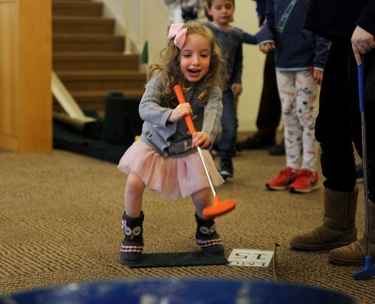 Abigail Herman, 4, of Fairfield, has fun during the Friends of the Library Mini-Golf fundraiser at the Fairfield Public Library in Fairfield, Conn. on Sunday, March 25, 2018. Holes were laid out through the stacks and down stairways and ramps throughout the building.