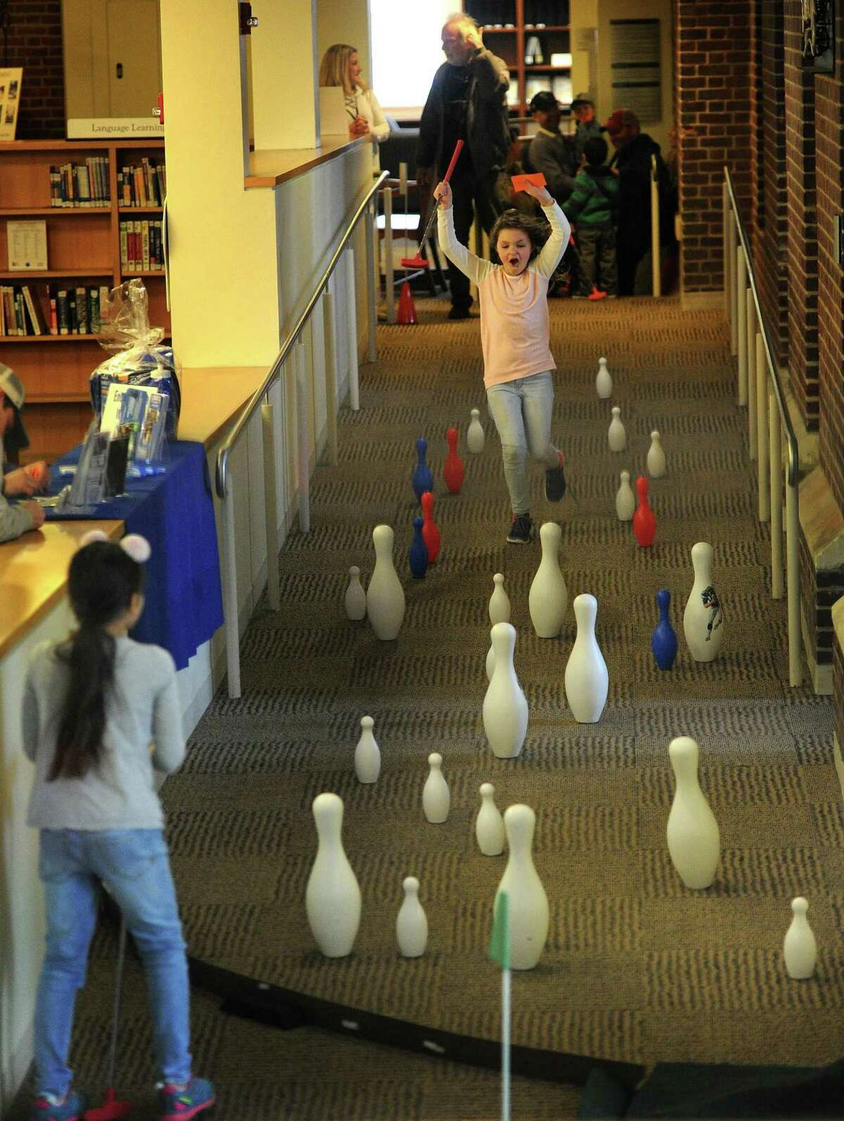 Friends Amanda Vielmetti and Ava Bossio, both 8, of Fairfield, have fun playing the 9th hole at the Friends of the Library Mini-Golf fundraiser at the Fairfield Public Library in Fairfield, Conn. on Sunday, March 25, 2018. Holes were laid out through the stacks and down stairways and ramps throughout the building.