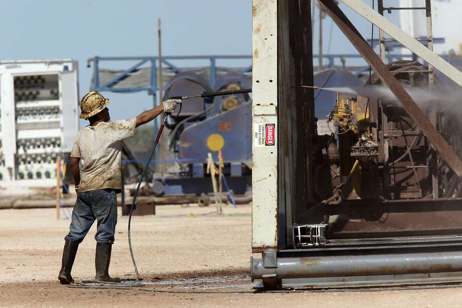 An oil worker washes off a drilling rig. Service companies led growth in the industry in the first quarter, according to the Dallas Fed. Photo: Jerry Lara /San Antonio Express-News / © 2012 San Antonio Express-News