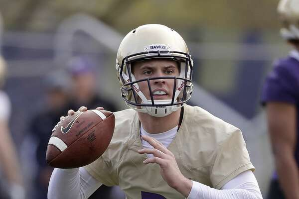 Washington quarterback Jake Browning looks to pass at the first practice of spring football for the NCAA college team Wednesday, March 28, 2018, in Seattle. (AP Photo/Elaine Thompson)