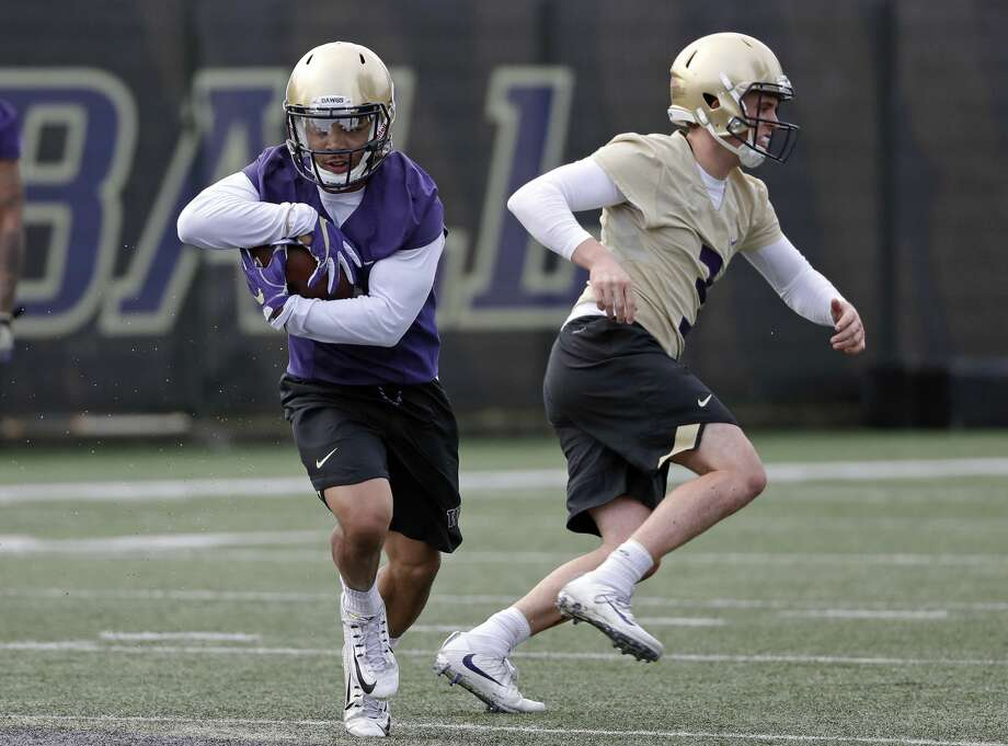 Washington's Myles Gaskin, left, runs after taking a handoff from quarterback Jake Browning during a drill at the first practice of spring football for the NCAA college team Wednesday, March 28, 2018, in Seattle. (AP Photo/Elaine Thompson) Photo: Elaine Thompson/AP