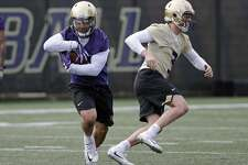 Washington's Myles Gaskin, left, runs after taking a handoff from quarterback Jake Browning during a drill at the first practice of spring football for the NCAA college team Wednesday, March 28, 2018, in Seattle. (AP Photo/Elaine Thompson)