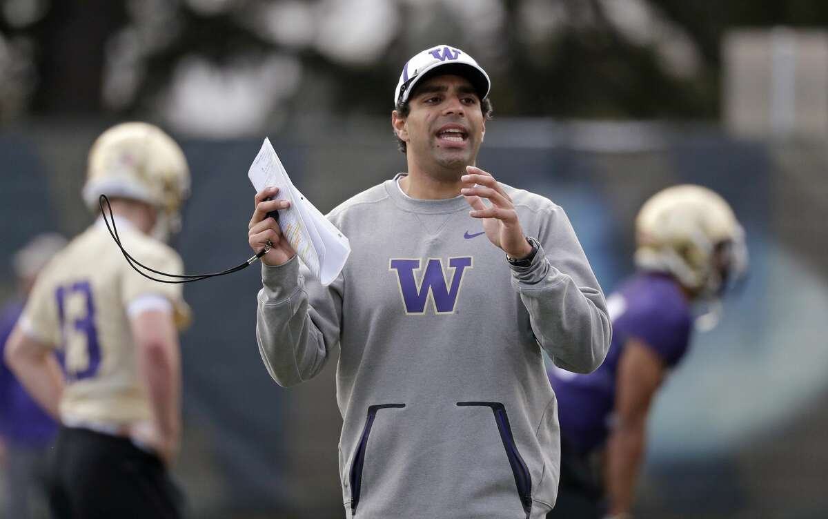 Washington offensive coordinator Bush Hamdan works with players at the first practice of spring football for the NCAA college team Wednesday, March 28, 2018, in Seattle. (AP Photo/Elaine Thompson)nam