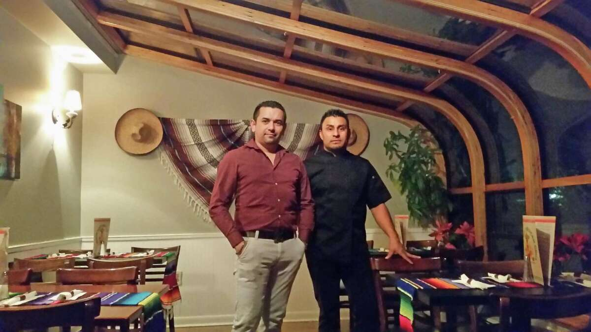 General manager Jose Reyes, left, and manager Fernando Galicia take a break on a busy night at Picante's in the wrap-around skylight porch room.