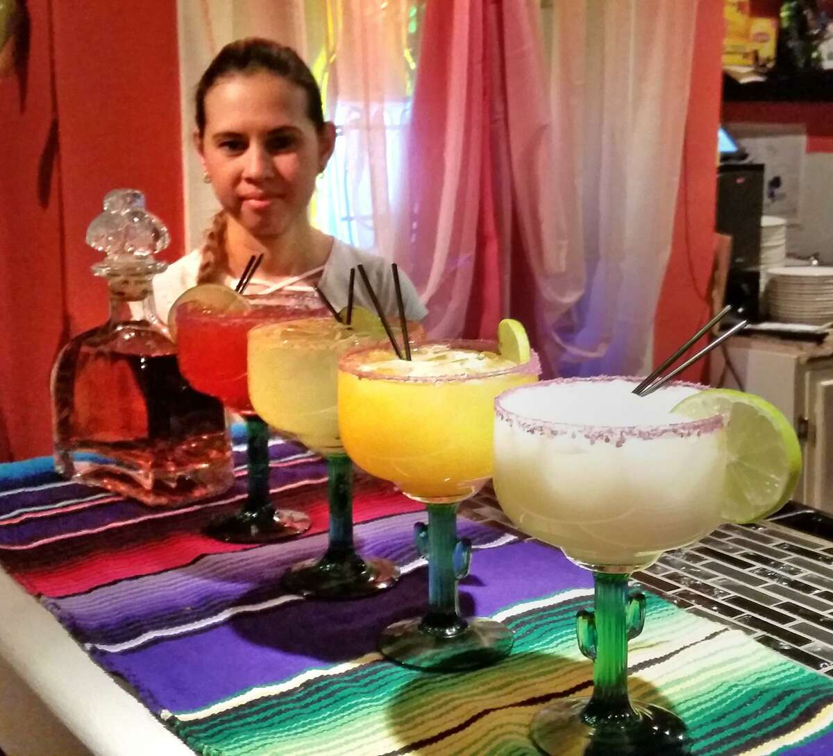 Server Reina Galicia, pictured with margaritas whose flavors range from traditional, mango, coconut and strawberry at Picante's.