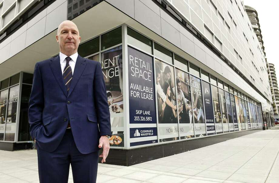 Skip Lane, a Stamford-based director for commercial real estate firm Cushman & Wakefield, stands on Tuesday, March 27, 2018, in front of the 325-unit Atlantic Station apartment tower at 355 Atlantic St., in downtown Stamford, Conn. The building includes about 17,000 square feet on its ground floor allocated for retailers and restaurants. Photo: Matthew Brown / Hearst Connecticut Media / Stamford Advocate