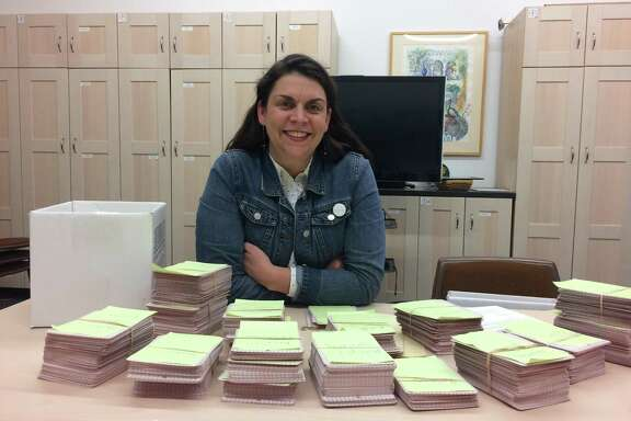 Kate Carey, head of education at the McNay Art Museum, sits with stacks of cards on which patrons shared survival stories during a retrospective of work by the late Chuck Ramirez. A reader commends the museum for this interactive approach.