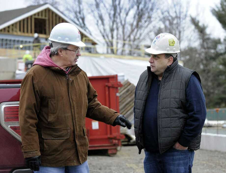 Jon Menti, left, chairman of the public site committee, and John Perna, a committee member, tour the new Bethel Police Station under construction in December. The 26,000-square-foot station is budgeted at $13.5 million but now has cost overruns of nearly $900,000. Photo: Carol Kaliff / Hearst Connecticut Media / The News-Times