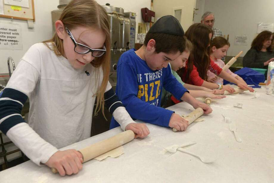 Congregation Beth El Rabbi Ita Paskind teaches students at their Hebrew school including Nina Rutherford, 11, and Robbie Eskenazi, 10, how to make matzo Tuesday at the synagogue in Norwalk. For the first time, Congregation Beth El-Norwalk has taken steps toward recognizing the increase in interfaith marriages, giving voting rights to family members who are not Jewish. In addition, it changed language regarding officers to be gender neutral. Photo: Erik Trautmann / Hearst Connecticut Media / Norwalk Hour
