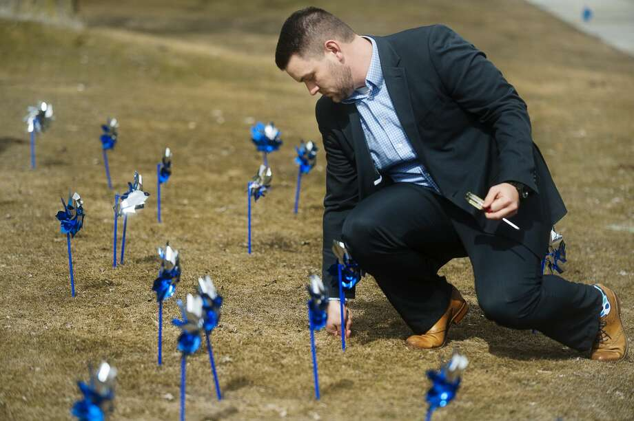 Coty Gould of Midland sticks a pinwheel into the ground in front of the Midland County Courthouse during a pinwheel ceremony on Wednesday, March 28, 2018 in honor of Child Abuse Prevention Month, celebrated every April. (Katy Kildee/kkildee@mdn.net) Photo: (Katy Kildee/kkildee@mdn.net)