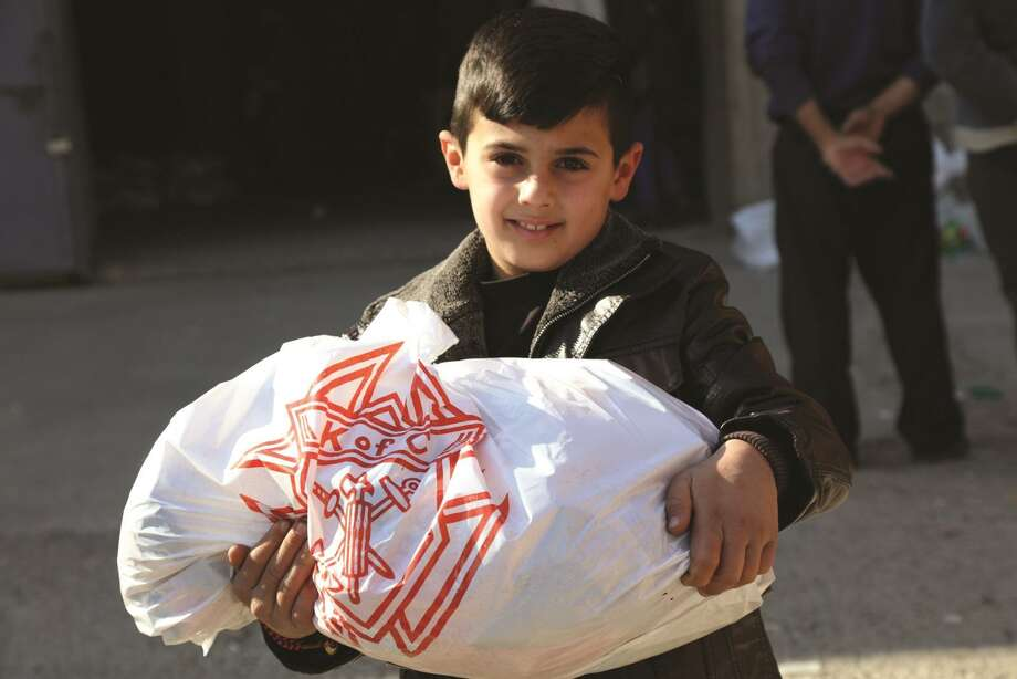 An Iraqi boy happily receives food provided by the Knights of Columbus. The Knights have committed more than $1 million to aid persecuted minority Christians in the Middle East, bringing their total to almost $19 million. Photo: Contributed Photo / Knights Of Columbus