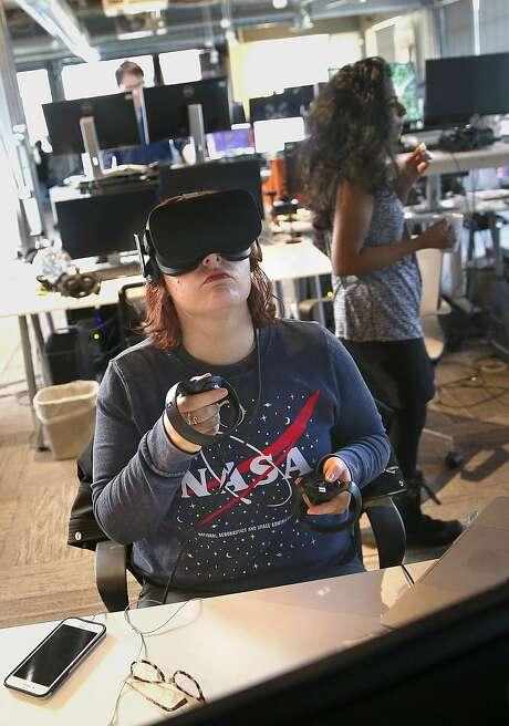 Media production associate Kayla Buchanan works on a medieval village VR demo at High Fidelity on Thursday in San Francisco. Photo: Liz Hafalia / The Chronicle