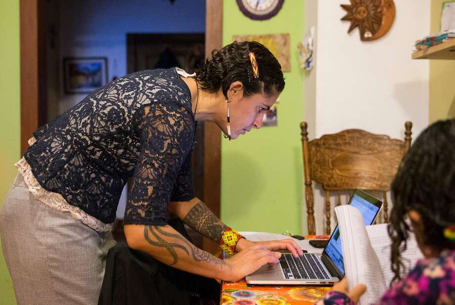 Lorena Melgarejo receives a notification about a possible ICE van near 20th and Valencia streets while doing work for the San Francisco Rapid Response Network at her home before taking her daughter to school. Photo: Jessica Christian / The Chronicle