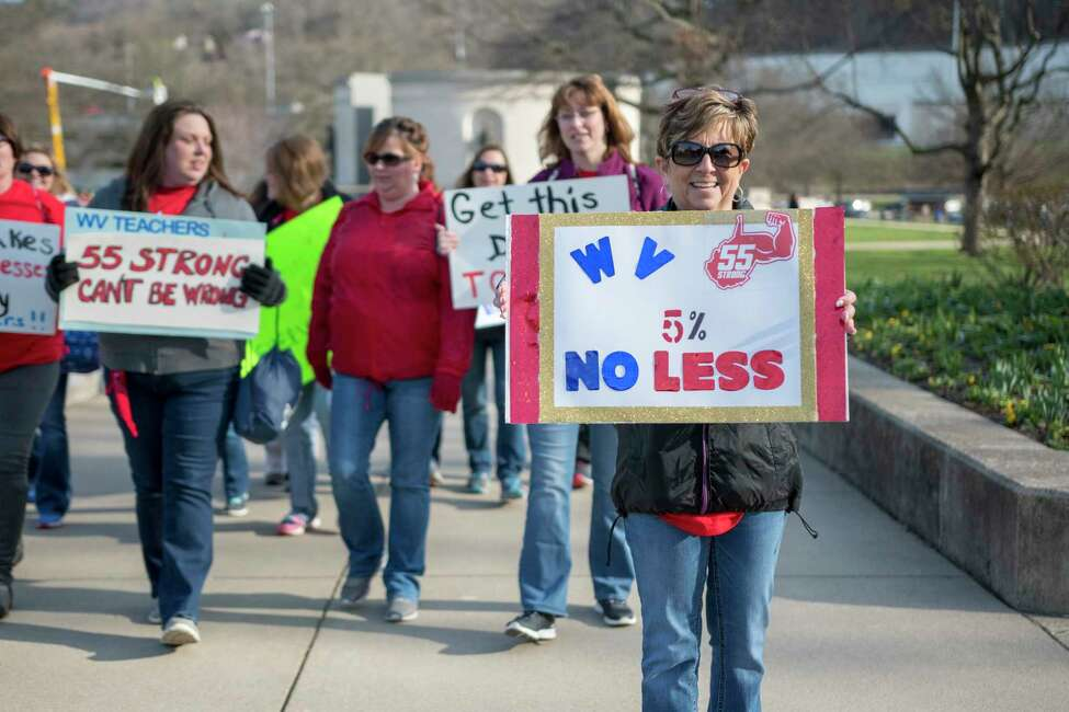 Elizabeth Ferguson Hollifield, a teacher from Princeton W.Va., holds a sign as she walks to a teacher rally Monday, March 5, 2018, at the West Virginia Capitol in Charleston, W.Va. Hundreds of teachers from 55 counties are on strike for pay raises and better health benefits. (AP Photo/Tyler Evert)