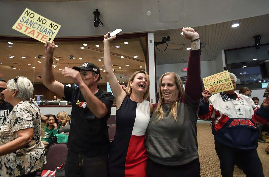 Left: David Hernandez, left, Genevieve Peters, center, and Jennifer Martinez celebrate after the Orange County Board of Supervisors voted to join the U.S. Department of Justice lawsuit against the State of California's sanctuary cities law (SB54) during their meeting in Santa Ana, Calif., Tuesday, March 27, 2018. (Jeff Gritchen/The Orange County Register via AP) Photo: Jeff Gritchen / Associated Press