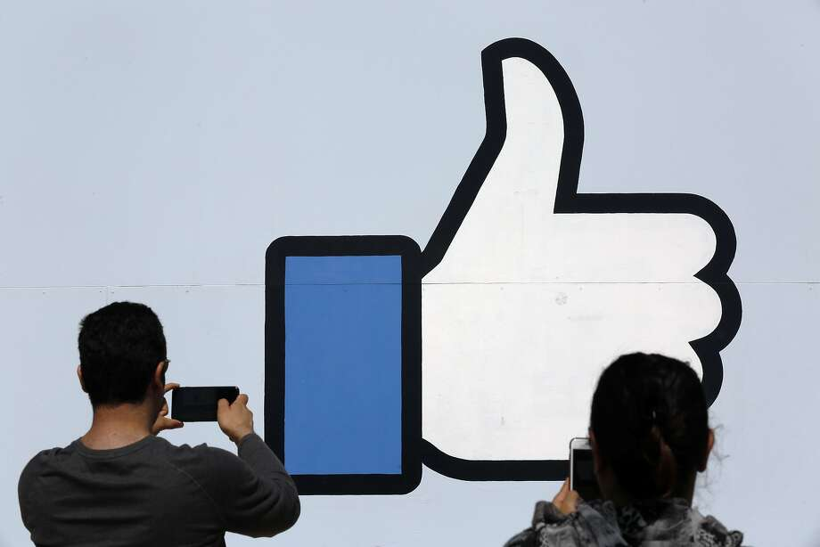 Visitors stop to take photos at the famous Facebook sign in front of corporate headquarters in Menlo Park. Photo: Michael Macor / The Chronicle