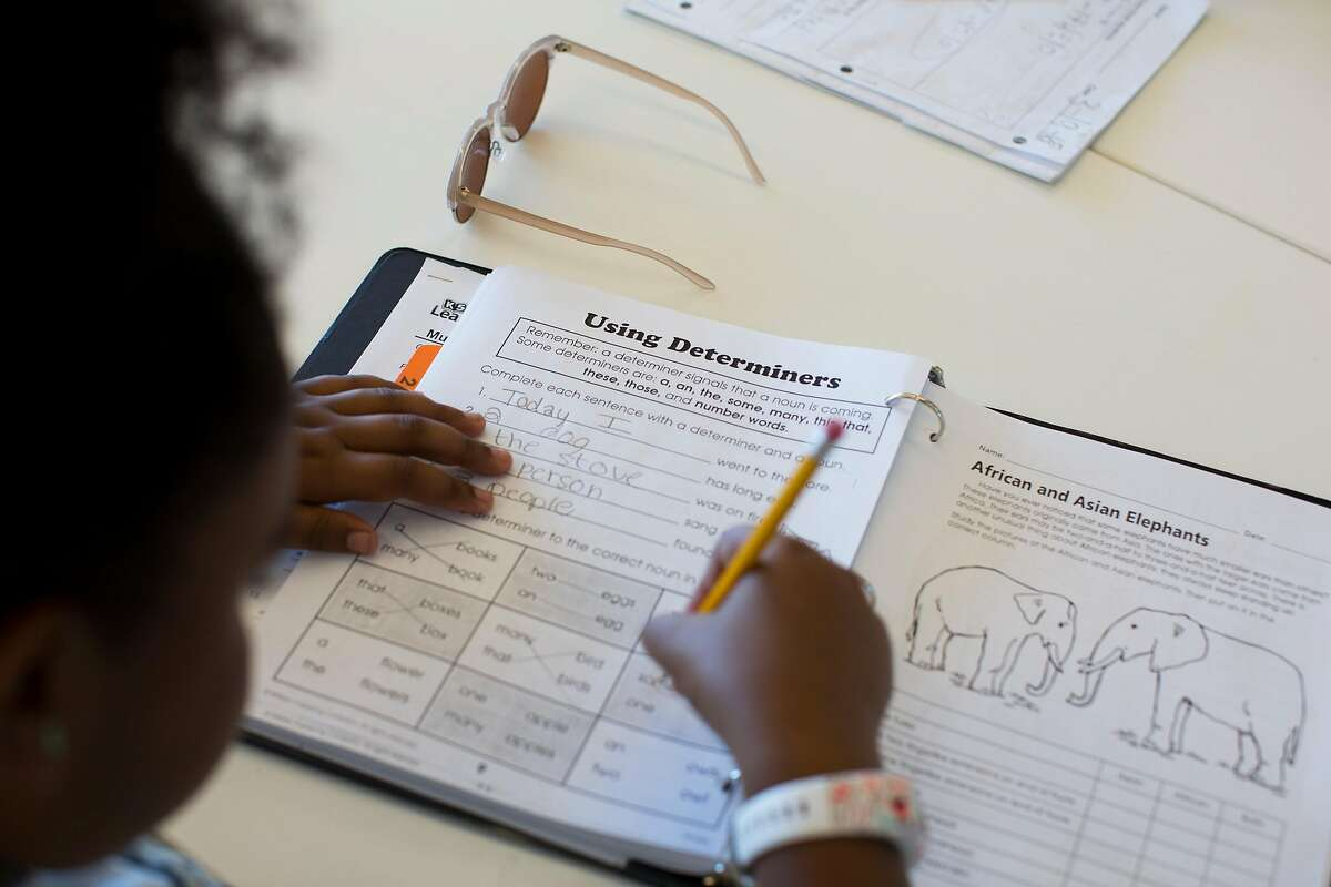 Amia Ignacio-Barnes, 9, works on homework after school at the Booker T Washington Community Services Center in San Francisco, Calif. A student at Washington High School in San Francisco received straight Fs for all four years. He got assistance and enrolled in a continuation school after he received mentoring at Booker T Washington Community Services Center.