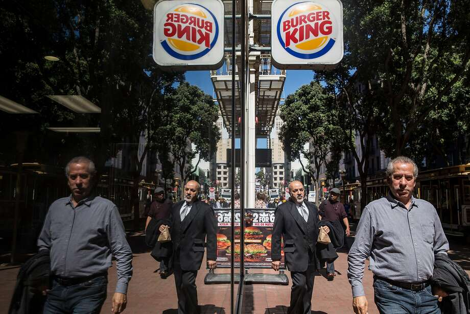 Big pic, above: A man exits Burger King on Powell Street with a to-go bag in hand Wednesday, March 28, 2018 in San Francisco, Calif. Second picture, left: Kris Croom writes in her journal after enjoying Burger King french fries as she sits outside Burger King on Powell Street Wednesday, March 28, 2018 in San Francisco, Calif. Photo: Jessica Christian / The Chronicle