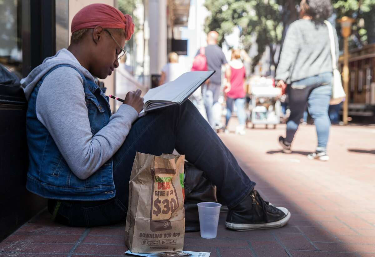 Kris Croom writes in her journal after enjoying Burger King french fries as she sits outside Burger King on Powell Street Wednesday, March 28, 2018 in San Francisco, Calif.