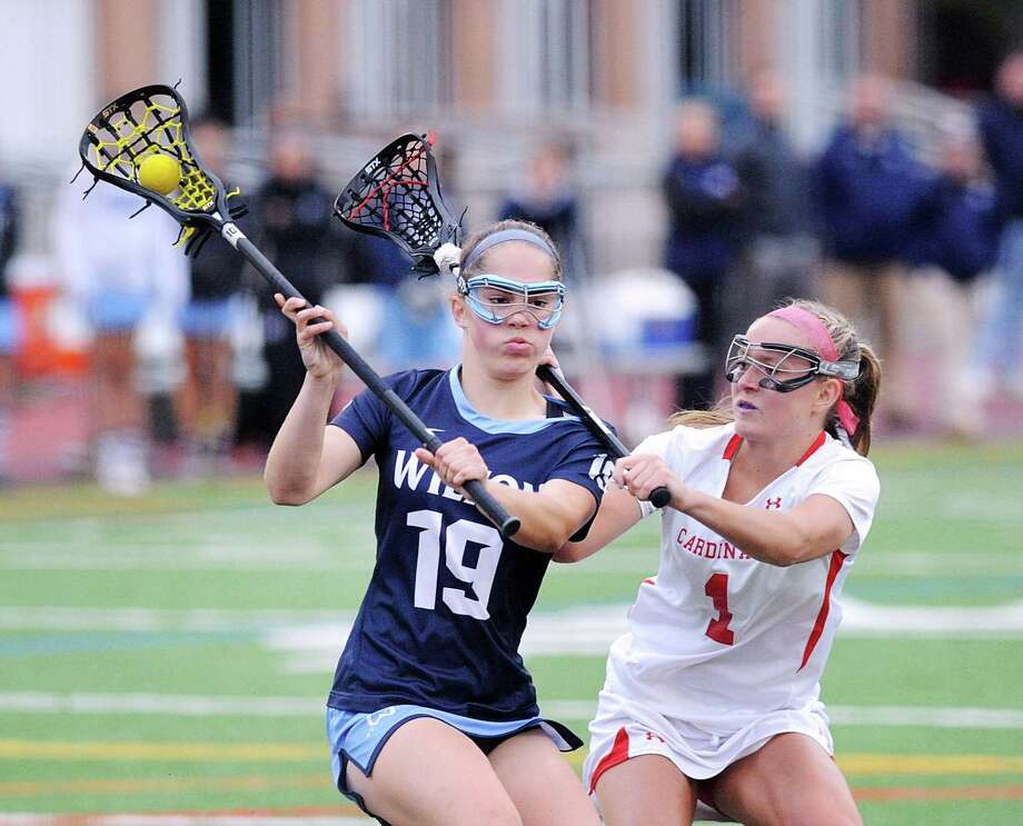 At left, Sophie Sudano (19) of Wilton is defended by Maggie O'Gorman (1) of Greenwich just before Sudano scored a goal during the second half of the CIAC Class L girls high school lacrosse semifinal match between Greenwich High School and Wilton High School at Brien McMahon High School in Norwalk, Conn., Tuesday, June 6, 2017. Wilton advanced with a 14-8 victory over Greenwich. Photo: Bob Luckey Jr. / Hearst Connecticut Media / Greenwich Time