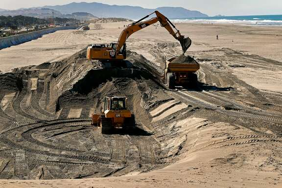 Huge dump trucks are filled with sand excavated from Ocean Beach near the Cliff House and transported to the other end to be used as erosion control in San Francisco, Calif. on Mon. Mar. 26, 2018. The San Francisco Public Utilities Commission  is moving 50,000 cubic yards of sand around at Ocean Beach as a stopgap measure for the erosion along the south end of the shoreline.