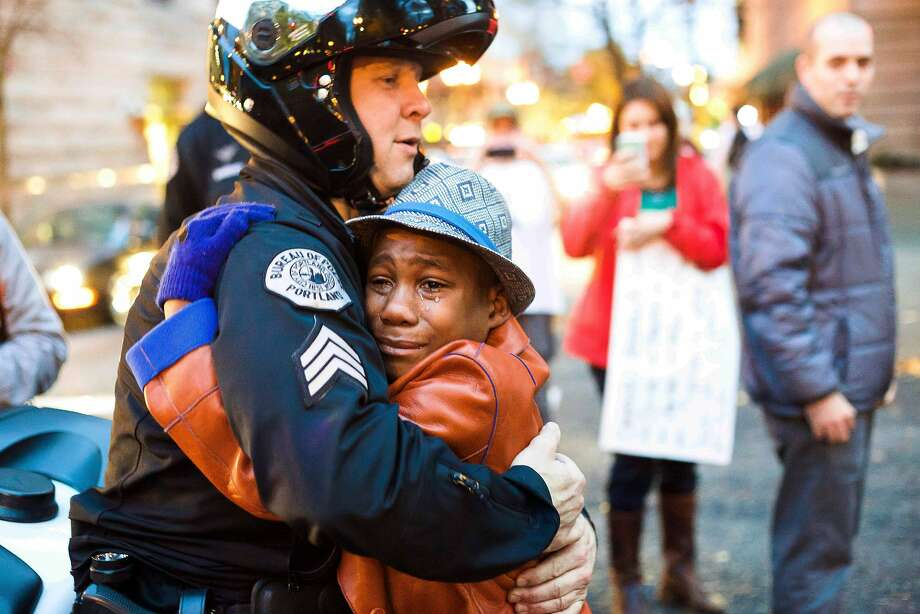 In this Tuesday, Nov. 25, 2014 photo provided by Johnny Nguyen, Portland police Sgt. Bret Barnum, left, and Devonte Hart, 12, hug at a rally in Portland, Ore., where people had gathered in support of the protests in Ferguson, Mo. Photo: Johnny Nguyen / Associated Press