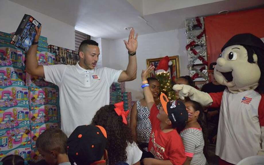 Astros shortstop Carlos Correa gives away toys and essentials at a charity event in Santa Isabel, P.R., two months after Hurricane Maria devastated his hometown  Photo: Russ Spielman / TLA
