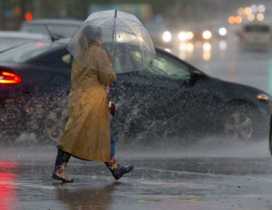 A woman walks with an umbrella through the intersection of Hildebrand Avenue and Broadway as cars splash by during a rainstorm that swept through San Antonio on Wednesday, March 28, 2018. More severe weather is expected this week. Photo: John Davenport /San Antonio Express-News / ©John Davenport/San Antonio Express-News