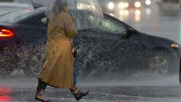 A woman walks with an umbrella through the intersection of Hildebrand Avenue and Broadway as cars splash by during a rainstorm that swept through San Antonio on Wednesday.