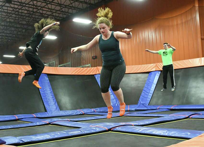 From left, Edwin Maldonado of Troy, Times Union reporter Leigh Hornbeck and Noah Powers of Latham take a SkyFit class at Sky Zone Trampoline Park on Wednesday, March 14, 2018 in Albany, N.Y. (Lori Van Buren/Times Union)