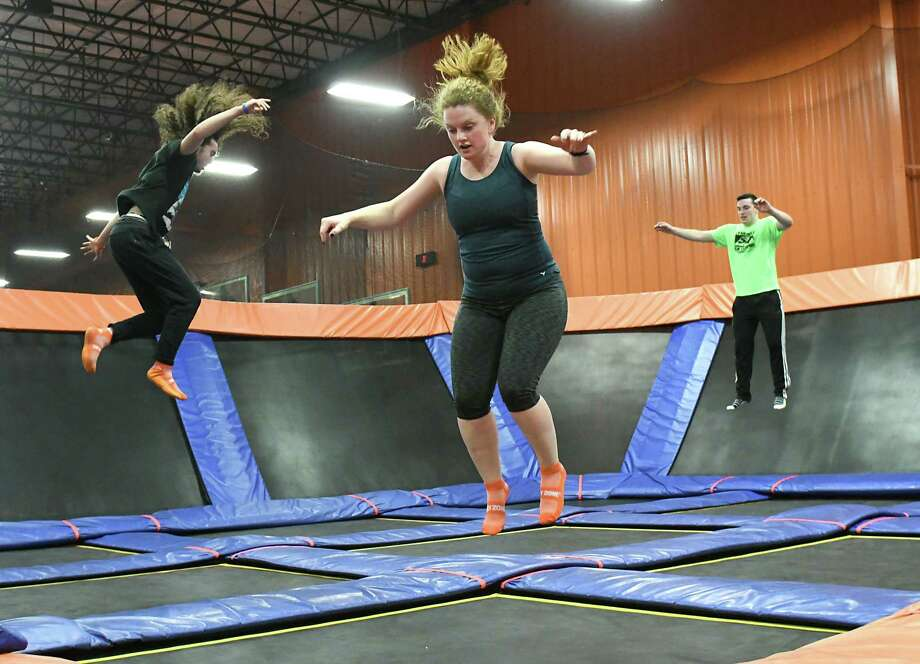 From left, Edwin Maldonado of Troy, Times Union reporter Leigh Hornbeck and Noah Powers of Latham take a SkyFit class at Sky Zone Trampoline Park on Wednesday, March 14, 2018 in Albany, N.Y. (Lori Van Buren/Times Union) Photo: Lori Van Buren / 20043073A