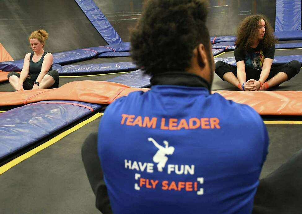 Instructor A. J. Burnett, center, has his students Times Union reporter Leigh Hornbeck, left, and Edwin Maldonado of Troy stretch at the end of a a SkyFit class at Sky Zone Trampoline Park on Wednesday, March 14, 2018 in Albany, N.Y. (Lori Van Buren/Times Union)