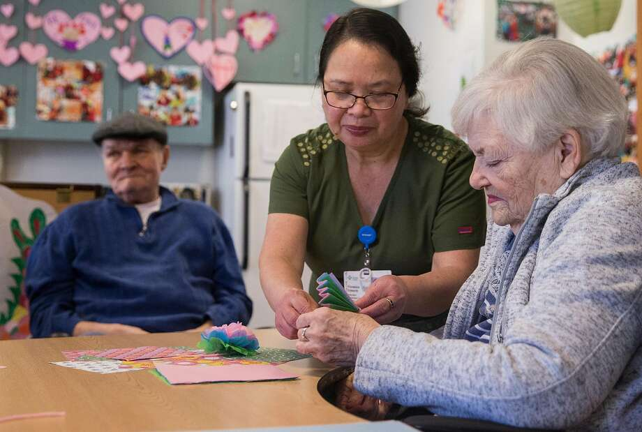 Staff member Flordeliza Edwards helps Lavonne Kleeman with crafts at the California Pacific Medical Center facility. Photo: Jessica Christian / The Chronicle
