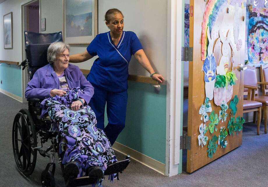 Azemera Abraha assists resident Margaret Bronfield before an art session at the Irene Swindells Alzheimer's care center. Photo: Photos By Jessica Christian / The Chronicle
