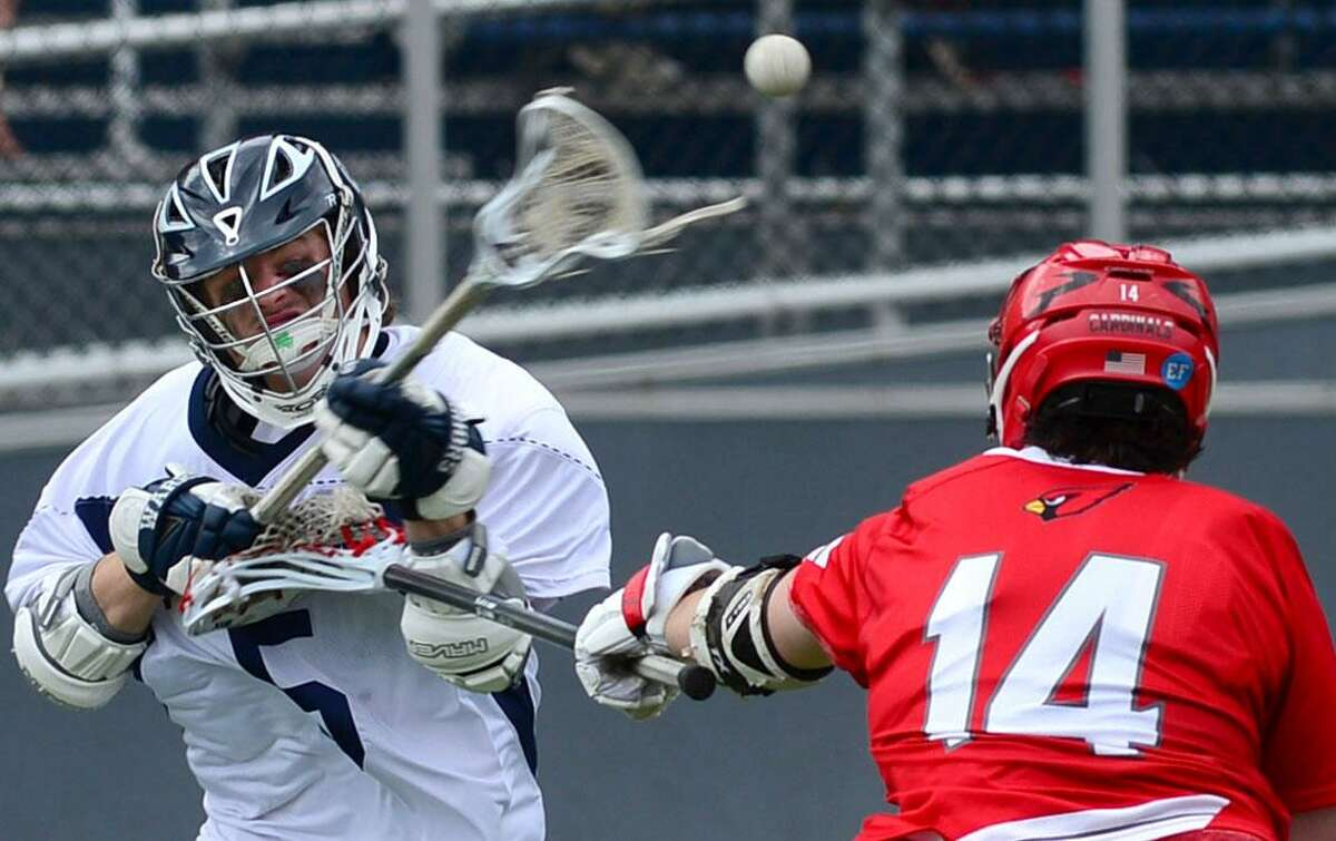#5 Joseph Murtha of the Wilton High School Warriors shoots past #14 Alex Bologna of the Greenwich Cardinals during their FCIAC boys lacrosse game Saturday, April 15, 2017, at Fujitani Field in Wilton, Conn.