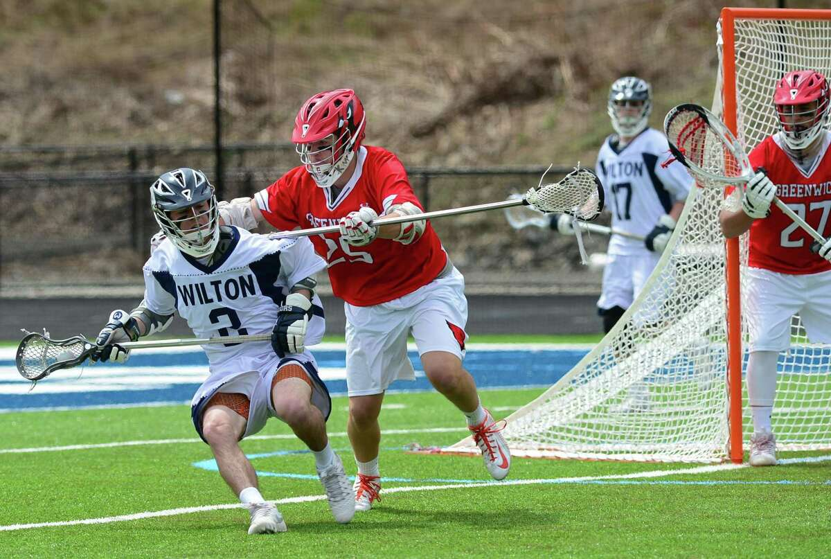 #2 Brian Calabrese of the Wilton High School Warriors battles #25 Luc Ayoub of the Greenwich Cardinals during their FCIAC boys lacrosse game Saturday, April 15, 2017, at Fujitani Field in Wilton, Conn.