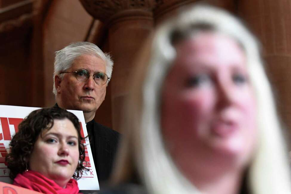 Rev. Peter Cook, executive director of the New York State Council of Churches, upper left, watches as Kat Sullivan, who says she was sexually abused and raped by a teacher at Troy's Emma Willard school 20 years ago, right, speaks while advocating for the Coalition to Pass the Child Victims Act on Wednesday, March 28, 2018, during a budget rally at the Capitol in Albany, N.Y. Advocates from Citizen Action, Common Cause, Coalition to Pass the Child Victims Act, Fiscal Policy Institute, New York Civil Liberties Union, Planned Parenthood Empire State Acts, New York State Council of Churches and others gathered for a joint rally in support of various items tied to the state budget. Cook is ordained in the United Church of Christ. (Will Waldron/Times Union)