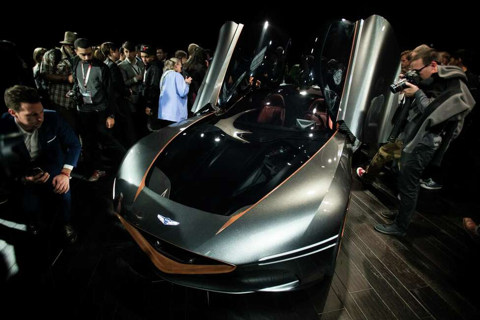 Attendees inspect the Hyundai Motor Co. Genesis Essentia concept plug-in GT luxury vehicle during the 2018 New York International Auto Show (NYIAS) in New York, U.S., on Wednesday, March 28, 2018. During the past few years, Genesis has used the New York show to launch a string of concepts aimed at luxury competitors, this time around the company revealed the Essentia, an all-electric coupe that is made from a super lightweight carbon-fiber monocoque body and sports a battery-powered motor that it says will get it to 60 mph in 3 seconds. Photographer: Mark Kauzlarich/Bloomberg
