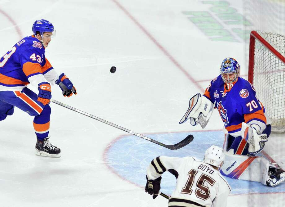 The puck caroms toward Sound Tigers defender Tyler Mueller (#43), left, after Sound Tigers goalie Kristers Gudlevskis (#70) made a stop on a shot by Travis Boyd (#15) of the Hershey Bears, right, during the second period of the AHL game between the Bridgeport Sound Tigers and the Hershey Bears at Webster Bank Arena in Bridgeport, Conn., Wednesday night, March 28, 2018. Photo: Bob Luckey Jr. / Hearst Connecticut Media / Greenwich Time