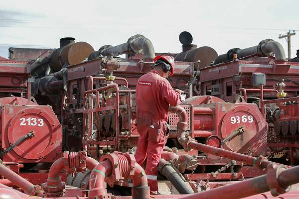 A Halliburton employee work near rows of hydraulic fracturing pumping units at a three pad site Monday, June 26, 2017, in Midland. ( Steve Gonzales / Houston Chronicle )