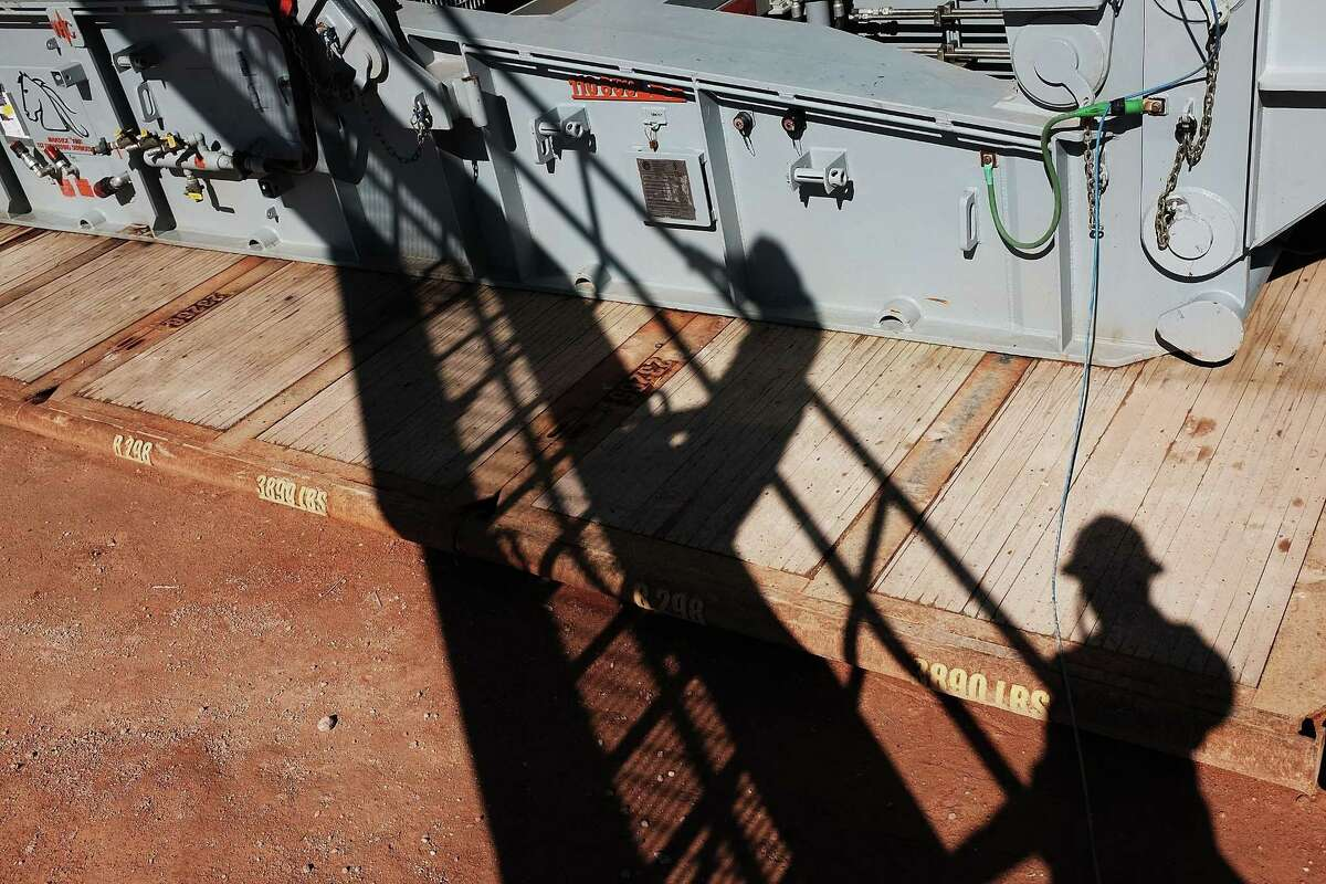 The shadows of workers with Apache Corp. are viewed at a site in the Permian Basin. Workers are in short supply as the drilling boom in West Texas continues.