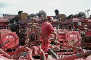 A Halliburton employee work near rows of hydraulic fracturing pumping units at a three pad site Midland.