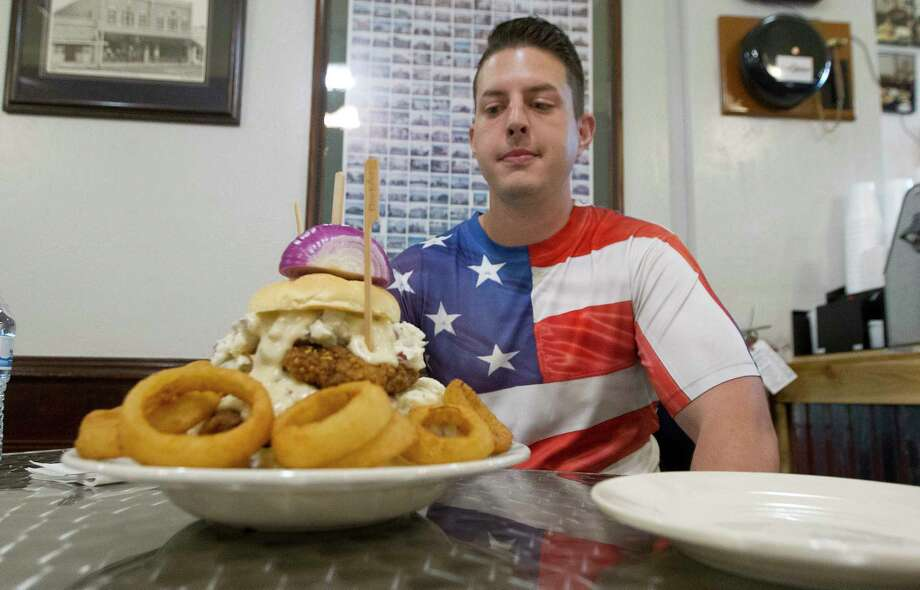 International food competitor Scott Collister looks upon his opponent, the Maxima Victus Chicken Fried Steak Challenge, at Red Onion Company, Wednesday, March 28, 2018, in Conroe. Challengers have 45 minutes to put away the 5-pound plate of food consisting of four slabs of children fried steak, mashed potatoes with gravy, lettuce, a half basket of onion rings and a red onion. Photo: Jason Fochtman, Staff Photographer / © 2018 Houston Chronicle