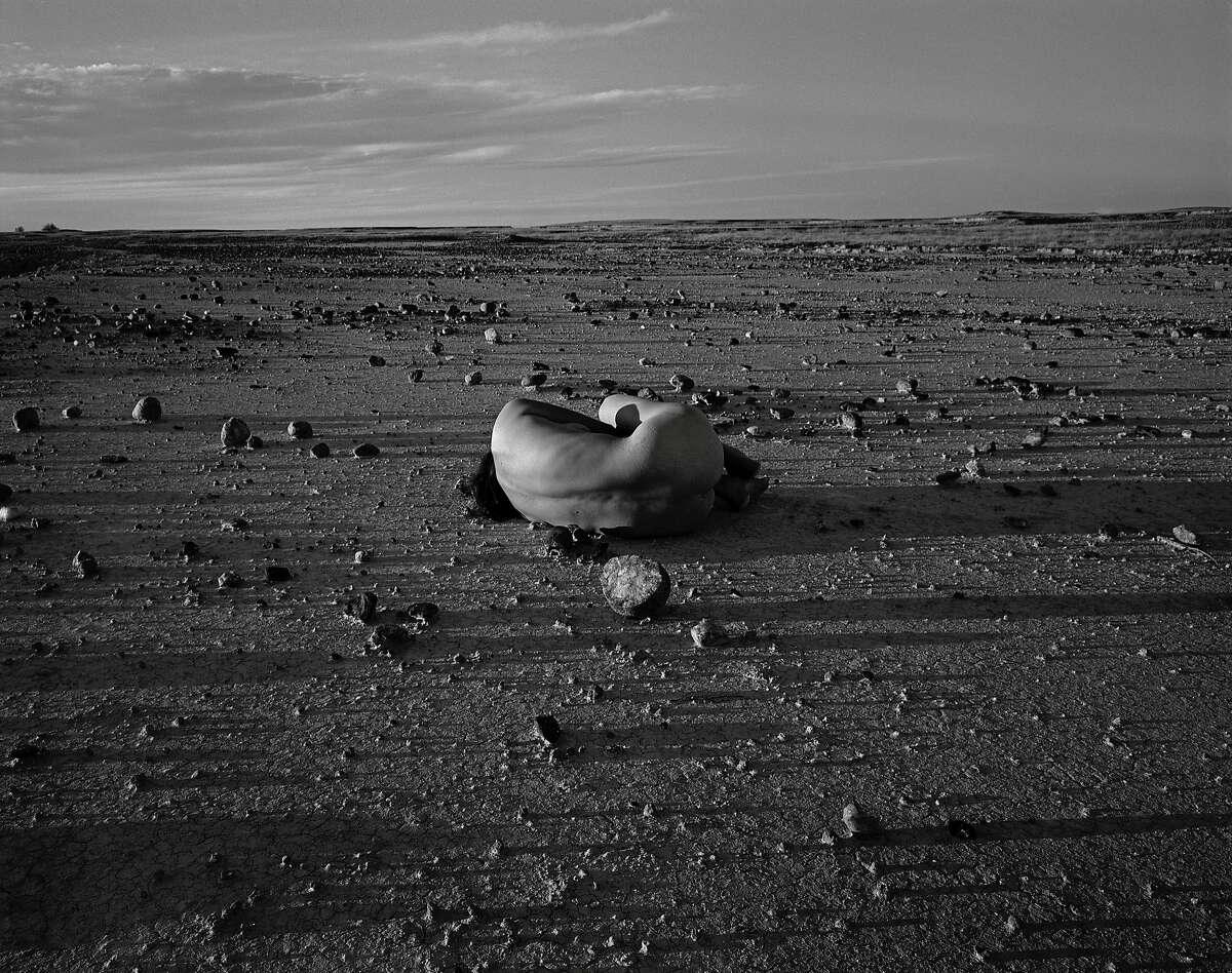 """Self-portrait with Stone.jpg Caption: Judy Dater, """"Self-portrait with Stone, Badlands, South Dakota,"""" 1981. Gelatin silver print, print: 14 3/8 x 18 � on 16 x 20 in. sheet. Collection of the artist. Credit: � Judy Dater Image Courtesy of the Fine Arts Museums of San Francisco"""