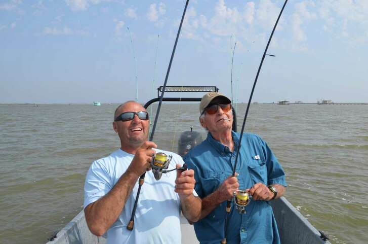 """A double hook-up on black drum lights up the faces of Capt. Joey Farah and his Dad, Joe Farah, during a birthday trip on Baffin Bay for the """"Old Salt"""" who taught his son everything he knows about saltwater angling and shares a father-son saltwater connection."""