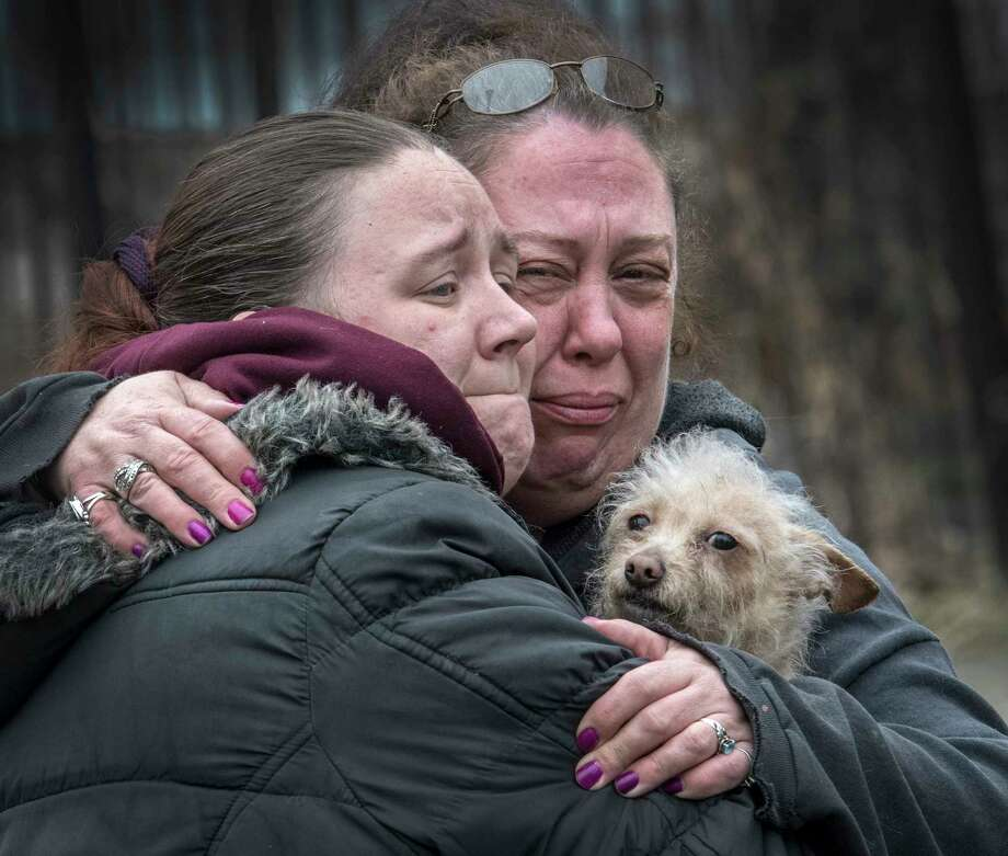 Residents of the fire building give one of the surviving pets a hug at the scene of a two-alarm fire at 158 6th Avenue Thursday March 29, 2018 in Troy, N.Y. A number of house pets were saved and a few were lost in the smokey blaze. (Skip Dickstein/Times Union) Photo: SKIP DICKSTEIN, Albany Times Union