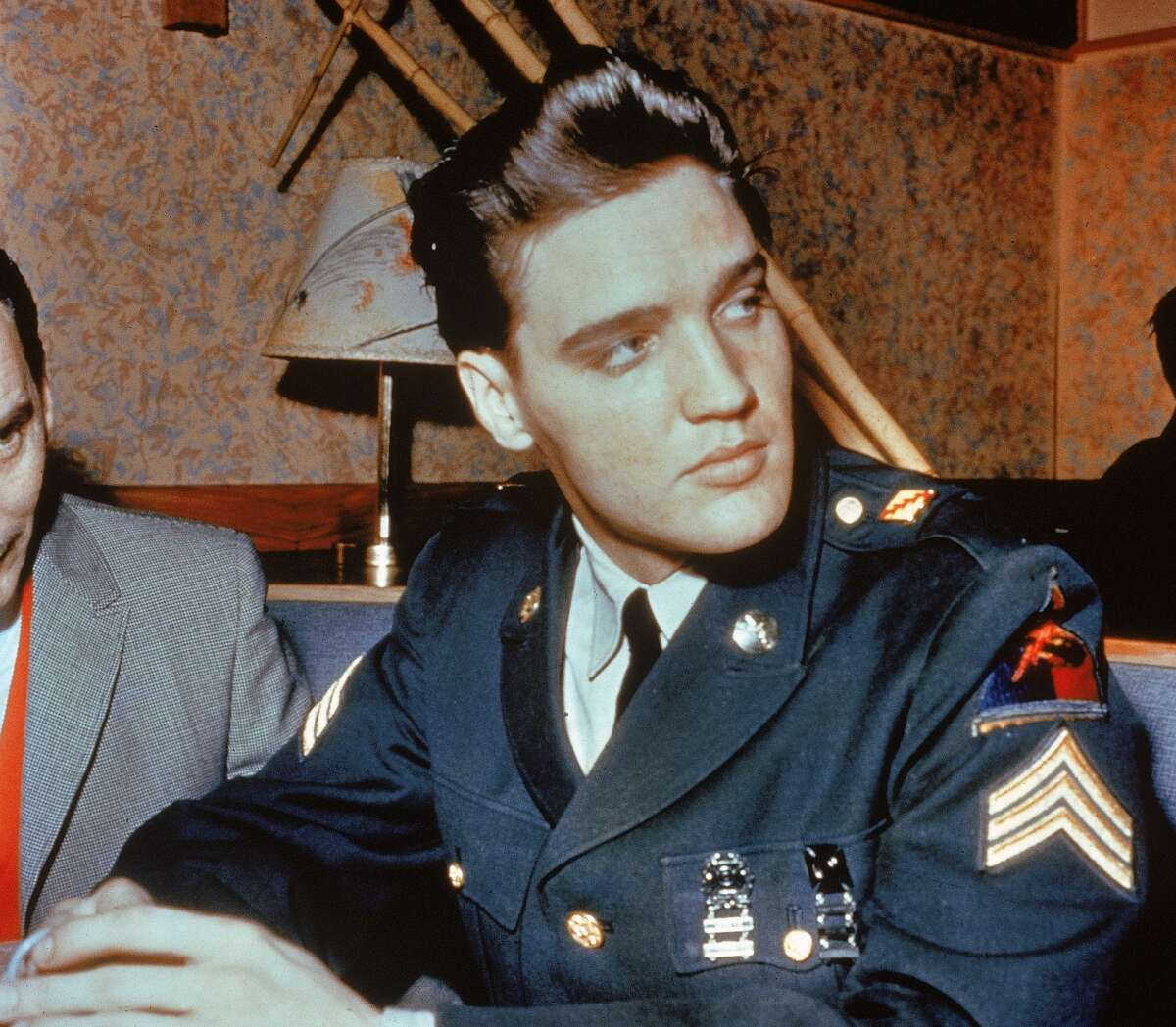 Circa 1958, American singer and actor Elvis Presley (1935 - 1977) sits in a restaurant wearing his US Army uniform. (Photo by Getty Images/Getty Images)