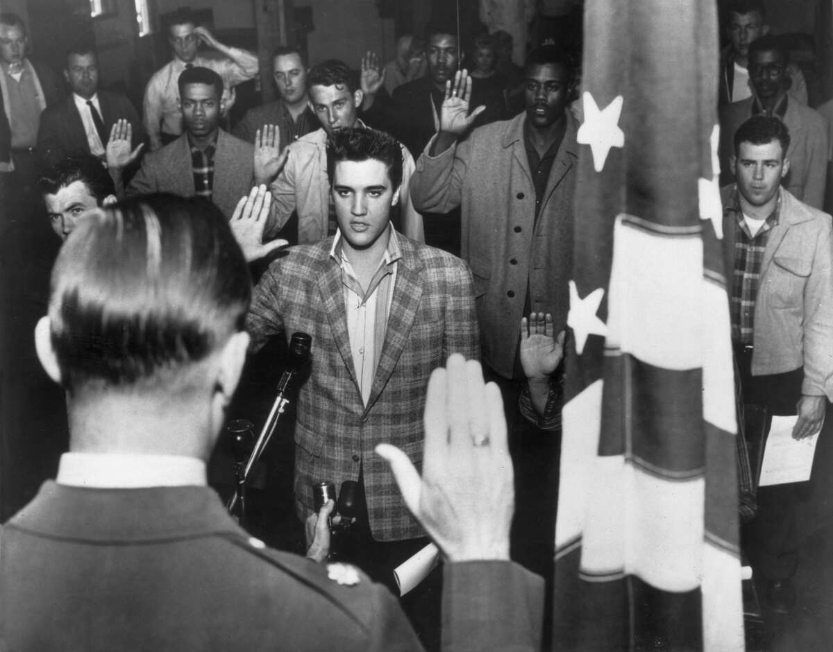 1958: American rock n' roll singer Elvis Presley (1935 - 1977) stands with a group of young men at an induction center, raising their right hands as they are sworn into the United States Army by an officer standing next to an American flag. (Photo by Hulton Archive/Getty Images)